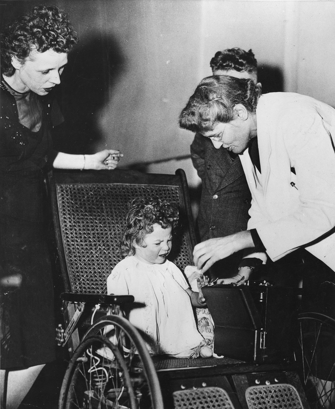 Helen Taussig, examining small girl in wheel chair, circa 1947