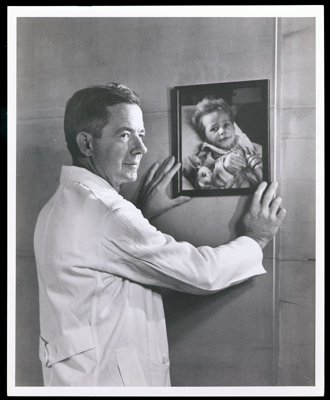 """""""Alfred Blalock hanging picture of baby, portrait photograph"""""""