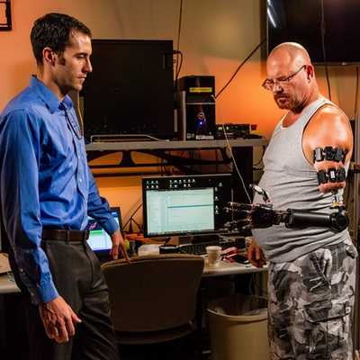 Dr. Mike McLoughlin outfitting veteran Johnny Matheny with a Myo-controlled prosthetic arm
