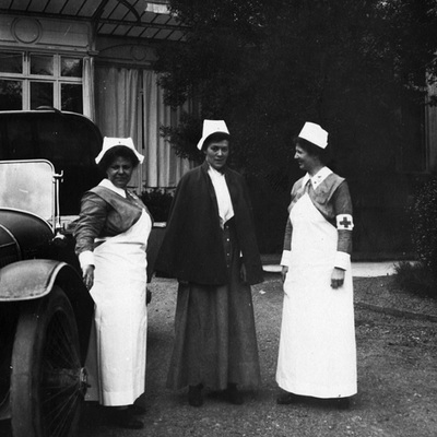 Unknown nurse, Alice Henderson and Vashti Bartlett, in driveway of Pau Hospital, standing by car